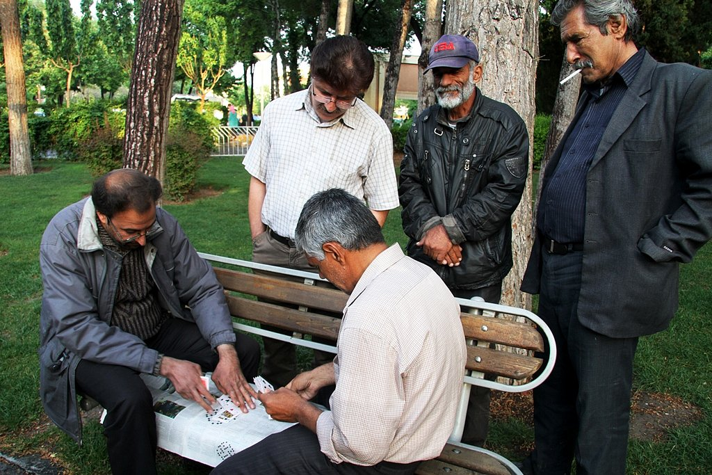 A group of men playing cards in a park in Isfahan.